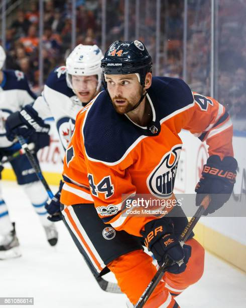 Zack Kassian of the Edmonton Oilers is watched by Jacob Trouba of the Winnipeg Jets at Rogers Place on October 9 2017 in Edmonton Canada