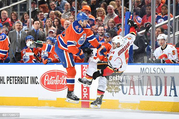 Zack Kassian of the Edmonton Oilers lands a big hit on Mark Giordano of the Calgary Flames on January 14 2017 at Rogers Place in Edmonton Alberta...