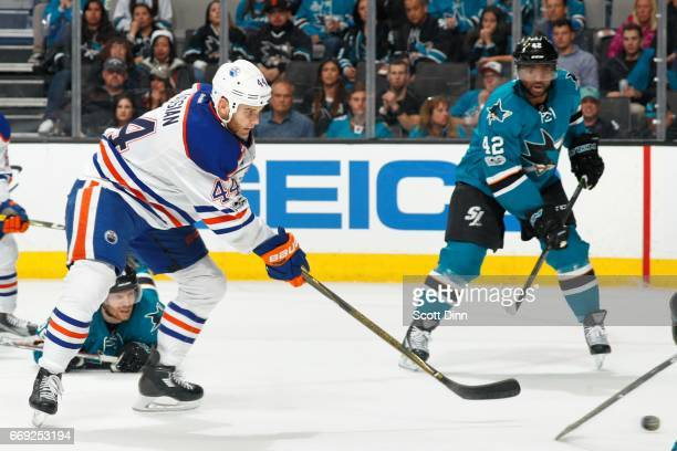 Zack Kassian of the Edmonton Oilers shoots the puck as Joel Ward of the San Jose Sharks looks in Game Three of the Western Conference First Round...