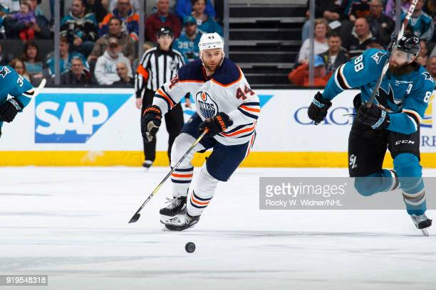 Zack Kassian of the Edmonton Oilers skates after the puck against Brent Burns of the San Jose Sharks at SAP Center on February 10 2018 in San Jose...
