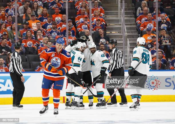 Zack Kassian of the Edmonton Oilers skates off as Joel Ward of the San Jose Sharks celebrates a goal in Game One of the Western Conference First...