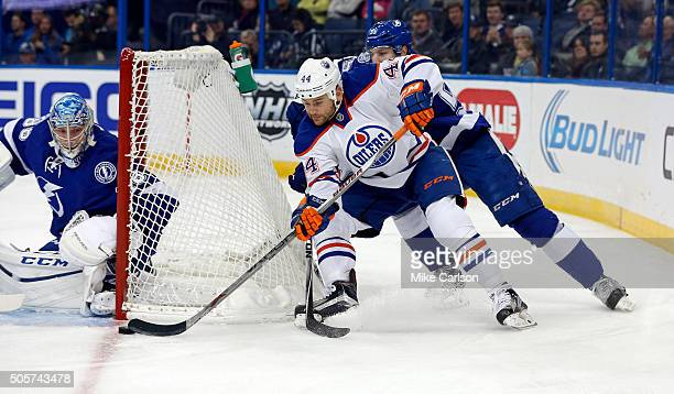 Zack Kassian of the Edmonton Oilers wraps around to goalie Andrei Vasilevskiy of the Tampa Bay Lightning as he's checked by Braydon Coburn during the...