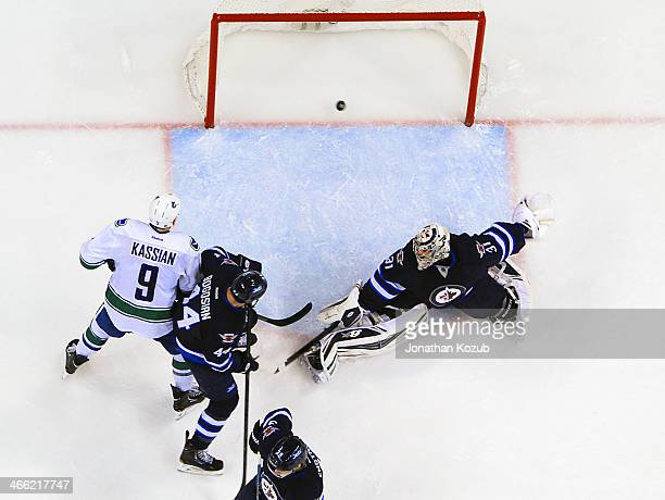 Zack Kassian of the Vancouver Canucks and Zach Bogosian of the Winnipeg Jets watch as the puck goes into the net behind goaltender Ondrej Pavelec for...