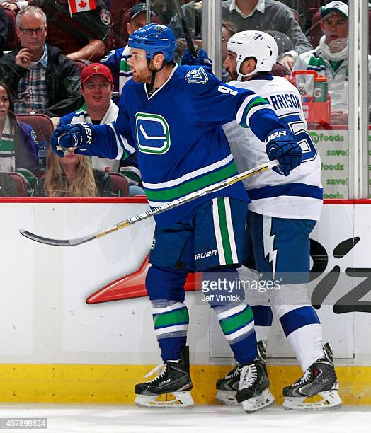 Zack Kassian of the Vancouver Canucks checks Jason Garrison of the Tampa Bay Lightning during their NHL game at Rogers Arena October 18, 2014 in...