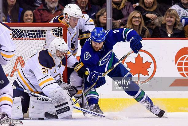 Zack Kassian of the Vancouver Canucks is stopped by goalie Matt Hackett of the Buffalo Sabres while Rasmus Ristolainen tries to help defend during...