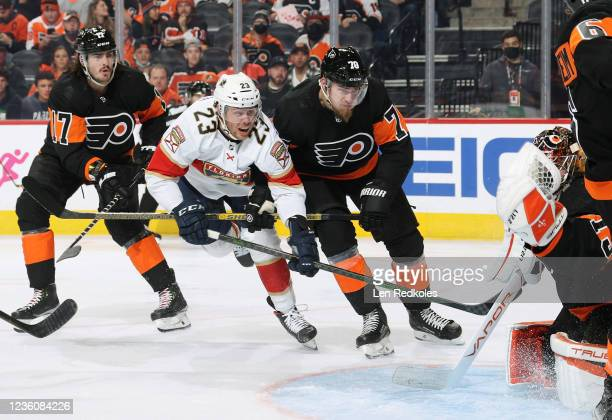 Zack MacEwen and Rasmus Ristolainen of the Philadelphia Flyers defend against Carter Verhaeghe of the Florida Panthers in front of Flyers goaltender...