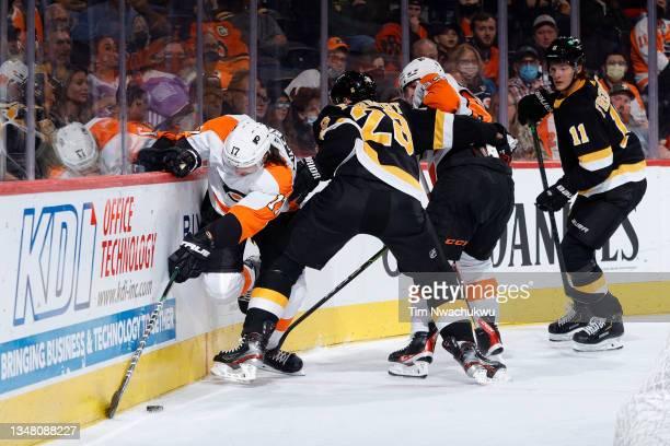 Zack MacEwen of the Philadelphia Flyers is guarded by Derek Forbort of the Boston Bruins at Wells Fargo Center on October 20, 2021 in Philadelphia,...