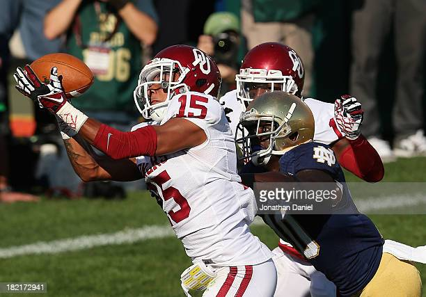 Zack Sanchez of the Oklahoma Sooners tries for an interception on pass intended for DaVaris Daniels of the Notre Dame Fighting Irish at Notre Dame...