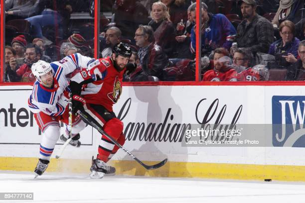 Zack Smith of the Ottawa Senators battles for the loose puck against David Desharnais of the New York Rangers at Canadian Tire Centre on December 13...