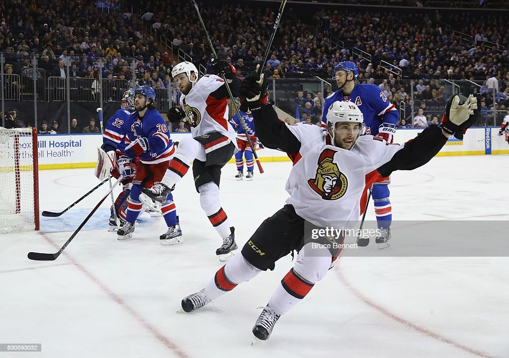 Zack Smith #15 of the Ottawa Senators (L) scores at 3:10 of the first period against Antti Raanta #32 of the New York Rangers as Derick Brassard #19 (R) joins the celebration at Madison Square Garden on December 27, 2016 in New York City.