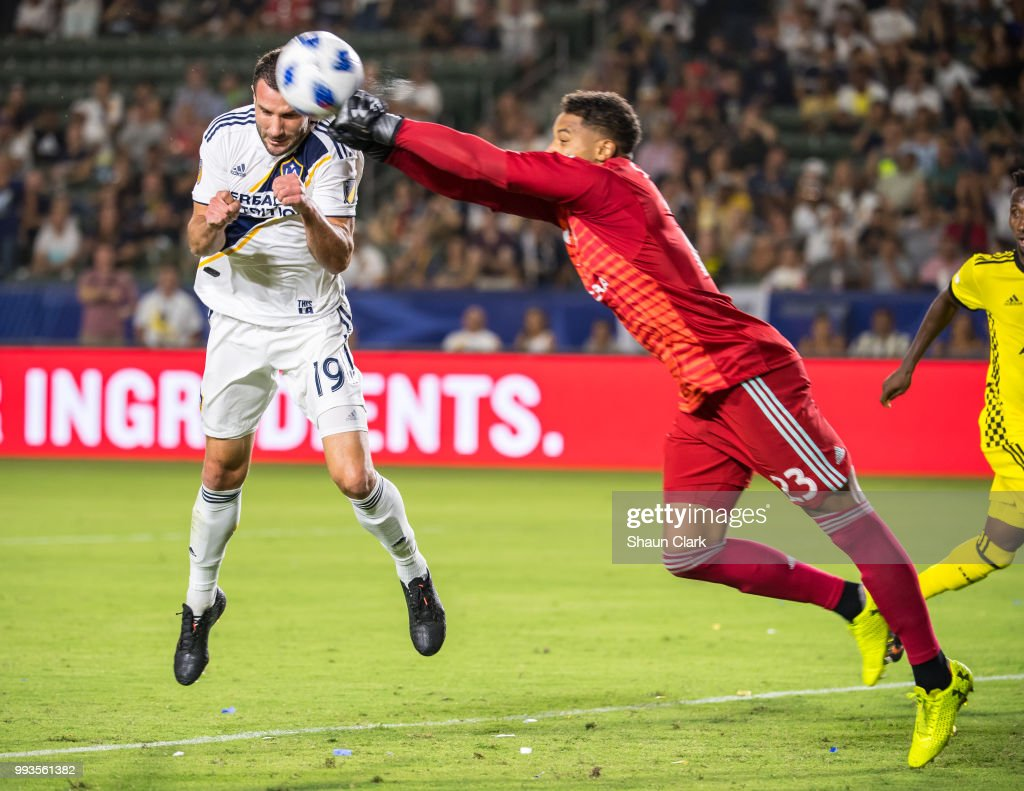 Zack Steffen #23 of Columbus Crew punches the ball clear as Chris Pontius #19 of Los Angeles Galaxy tries to get on the end of a cross during the Los Angeles Galaxy's MLS match against Columbus Crew at the StubHub Center on July 7, 2018 in Carson, California. Los Angeles Galaxy won the match 4-0