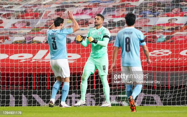 Zack Steffen of Manchester City celebrates with Ruben Dias of Manchester City after making a save during the Carabao Cup Semi Final match between...