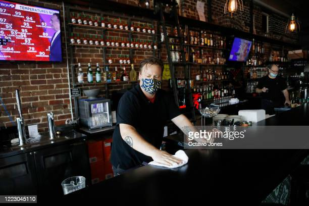 Zack Vermes a bartender at Carmines Ybor Italian restaurant wipes off the bar while awaiting patrons on June 26 2020 in Tampa Florida...