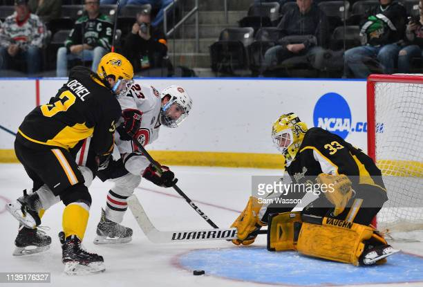 Zackarias Skog of the American International Yellow Jackets makes a save against Robby Jackson of the St Cloud State Huskies as Patrik Demel of the...