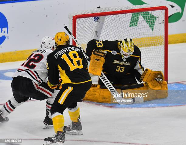 Zackarias Skog of the American International Yellow Jackets stops a shot as Jack Ahcan of the St Cloud State Huskies and Blake Christensen of the...