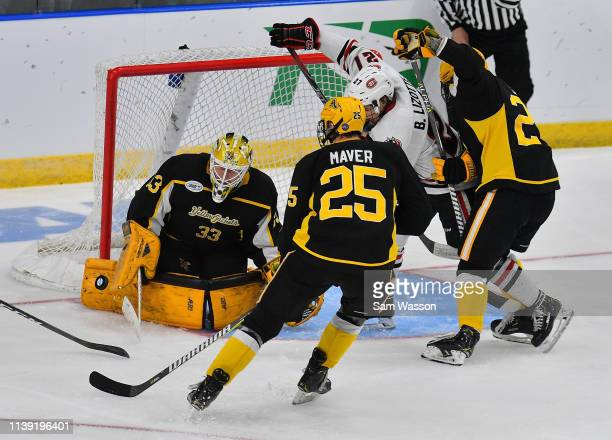 Zackarias Skog of the American International Yellow Jackets stops a St Cloud State Huskies' shot as Blake Lizotte of the Huskies waits for a rebound...