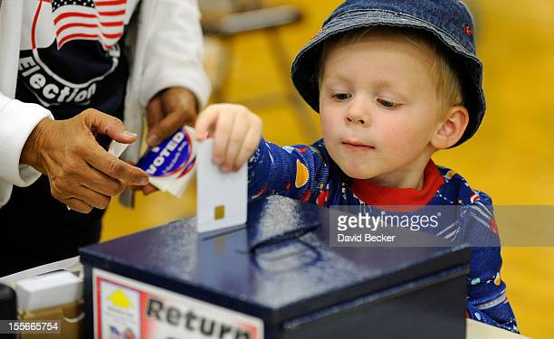 Zackary Lea returns his mother's authorization card after she cast her ballot at John Fremont Middle School on November 6 2012 in Las Vegas Nevada...