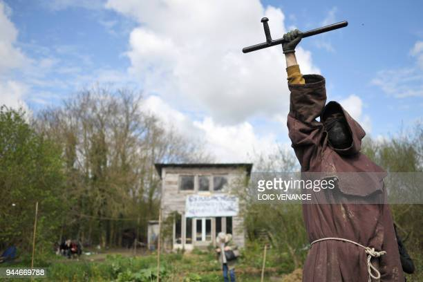 Zad activist raises a Tonfa in front of a wooden caban as clashes erupt on April 11 2018 during a police operation to raze the decadeold camp known...