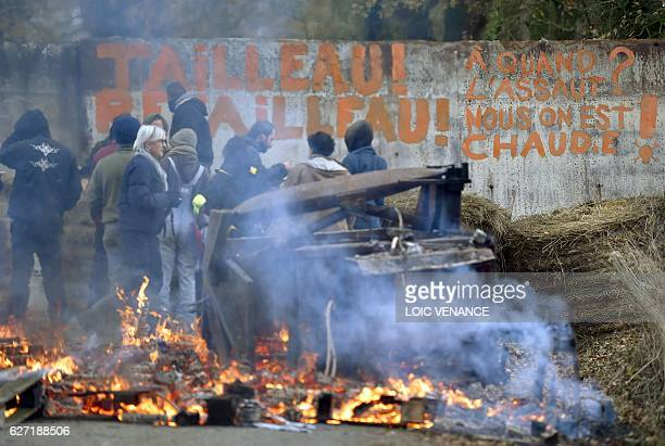 Zad activists stand in front of a the inscription 'Tailleau Retailleau' on a barricade to block the access of the Bellevue farm in the 'zad' of...