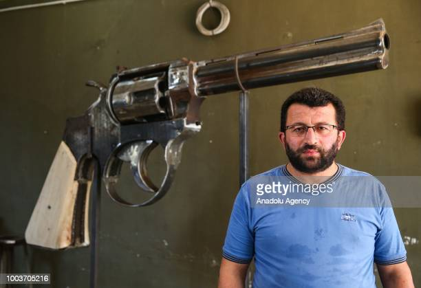 Zafer Erdem who is a kinetic sculptor from Rize is seen near his own product 100kg giant iron weapon in Istanbul Turkey on July 22 2018 Making the...