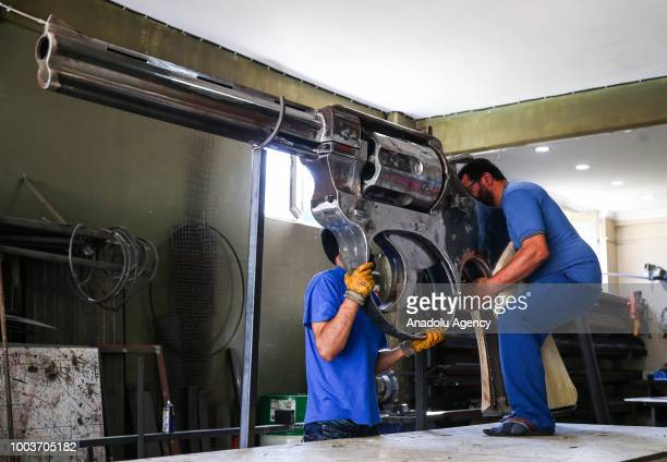 Zafer Erdem who is a kinetic sculptor from Rize is seen next to his own product 100kg giant iron weapon in Istanbul Turkey on July 22 2018 Making the...
