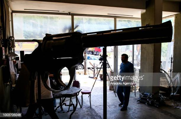 Zafer Erdem who is a kinetic sculptor from Rize is seen with his own product 100kg giant iron weapon in Istanbul Turkey on July 22 2018 Making the...