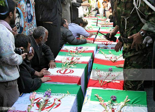 Iranian men mourn over coffins during the funeral of 11 Revolutionary Guards who were killed two days ago when a boobytrapped car exploded in front...