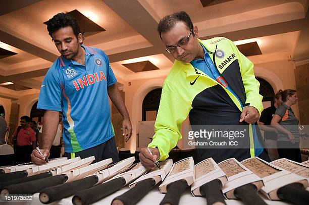 Zaheer Khan and Virender Sehwag of India sign bats during a portrait session at the Taj Samudra hotel on September 14 2012 in Colombo Sri Lanka