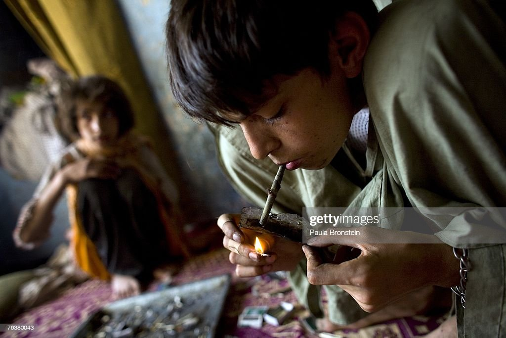 Zaher, 14, (R) smokes heroin along side his mother Sabera and sister Gulparai, 12, (L) August 27, 2007 in Kabul, Afghanistan. Zaher's mother, Sabera, a widow, has been smoking for four years since she lost her husband. Her children, Gulparai and Zaher began smoking two years ago after watching their mother. The cost for daily use of the drug is around $3.00 USD or 150 in Afghani currency. Farmers in the Taliban-held areas of the south are also urged to grow opium. Although there are around 35,000 NATO troops in Afghanistan, the drug trade has increased, with Afghanistan producing 95 percent of the world's poppies. According to the UN Office on Drugs and Crime (UNODC), the opium production in 2006 increased 57 percent from 2005, with an additional 15% jump in 2007 despite a $600 million counter narcotics effort by the U.S.
