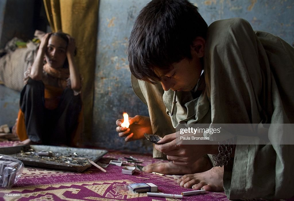 Zaher, 14, smokes heroin along side his mother Sabera and sister Gulparai, 12, (L) August 27, 2007 in Kabul, Afghanistan. Zaher's mother, Sabera, a widow, has been smoking for four years since she lost her husband. Her children, Gulparai and Zaher began smoking two years ago after watching their mother. The cost for daily use of the drug is around $3.00 USD or 150 in Afghani currency. Farmers in the Taliban-held areas of the south are also urged to grow opium. Although there are around 35,000 NATO troops in Afghanistan, the drug trade has increased, with Afghanistan producing 95 percent of the world's poppies. According to the UN Office on Drugs and Crime (UNODC), the opium production in 2006 increased 57 percent from 2005, with an additional 15% jump in 2007 despite a $600 million counter narcotics effort by the U.S.
