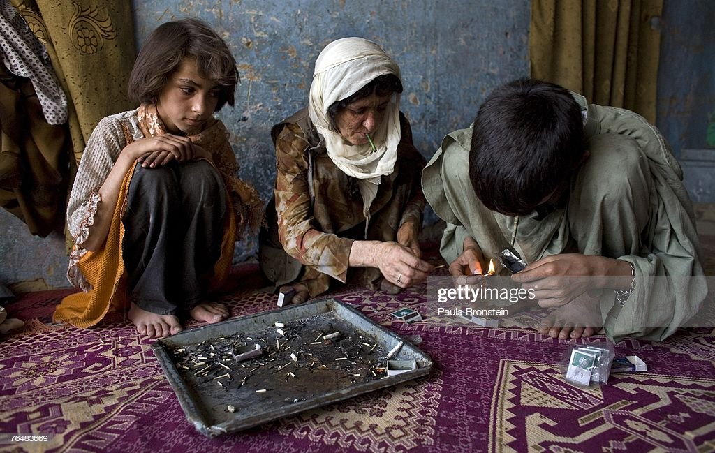 Zaher, 14, (R) smokes heroin along side his mother Sabera (C) and sister Gulparai, 12, (L) August 27, 2007 in Kabul, Afghanistan. Zaher's mother, Sabera, a widow, has been smoking for four years since she lost her husband. Her children, Gulparai and Zaher began smoking two years ago after watching their mother. The cost for daily use of the drug is around $3.00 USD or 150 in Afghani currency. Farmers in the Taliban-held areas of the south are also urged to grow opium. Although there are around 35,000 NATO troops in Afghanistan, the drug trade has increased, with Afghanistan producing 95 percent of the world's poppies. According to the UN Office on Drugs and Crime (UNODC), the opium production in 2006 increased 57 percent from 2005, with an additional 15% jump in 2007 despite a $600 million counter narcotics effort by the U.S.