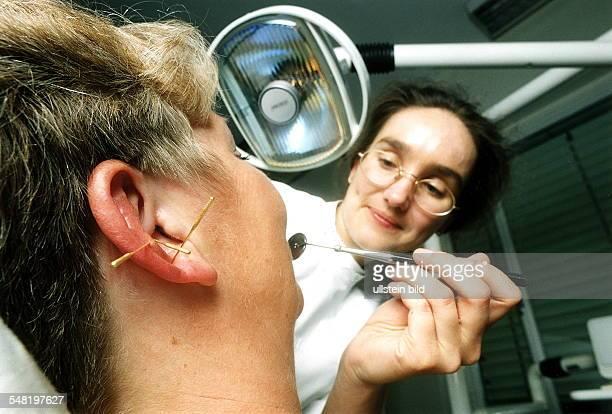 Zahnärztin behandelt eine Patientin Zur Betäubung der Schmerzen wurde der Patientin das Ohr akupunktiert 00071996