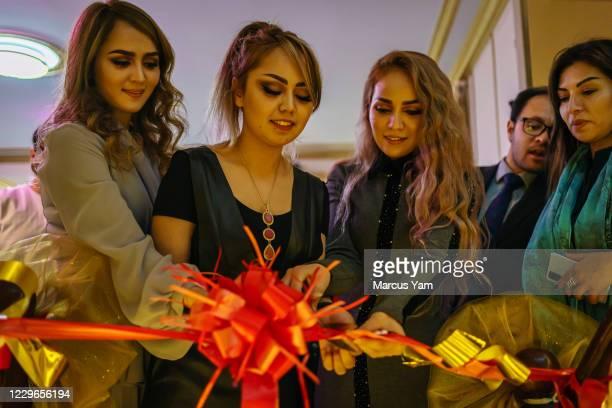 Zaiban Shahidy, from left, Soraya Shahidy, and Freshta Shahidy, cut a large ribbon to commemorate the opening of their family-owned beauty salon they...