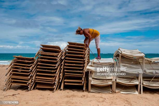 TOPSHOT Zaida Elena chains up beach chairs from her rental business in El Condado tourist zone in San Juan Puerto Rico on March 18 2020 On Sunday...