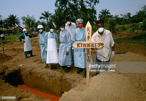 Zairean men in surgical scrubs masks and other protective clothing stand next to the grave of an Ebola virus victim The 1995 Ebola epidemic killed...