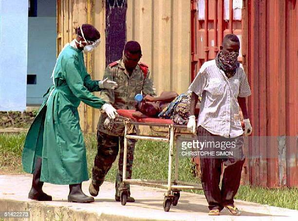 Zairean soldier and a civilian carry a patient affected by the deadly Ebola virus 14 May as a doctor follows them to the hospital in the city of...