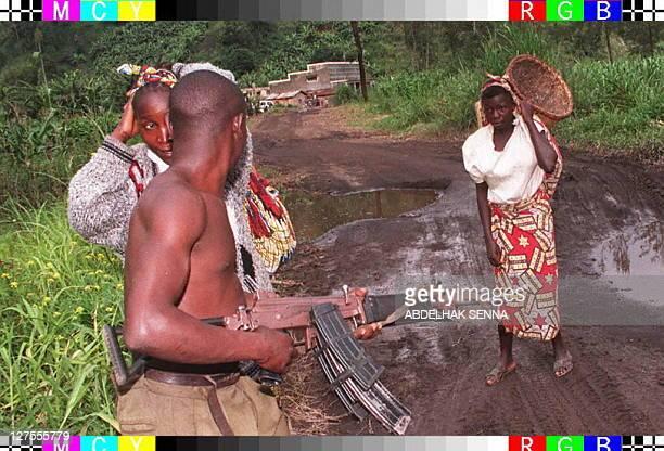 A Zairean Tutsi rebel holds his Kalashnikov 28 november while refugees make their way through the town of Sake western Goma Canadian General Maurice...