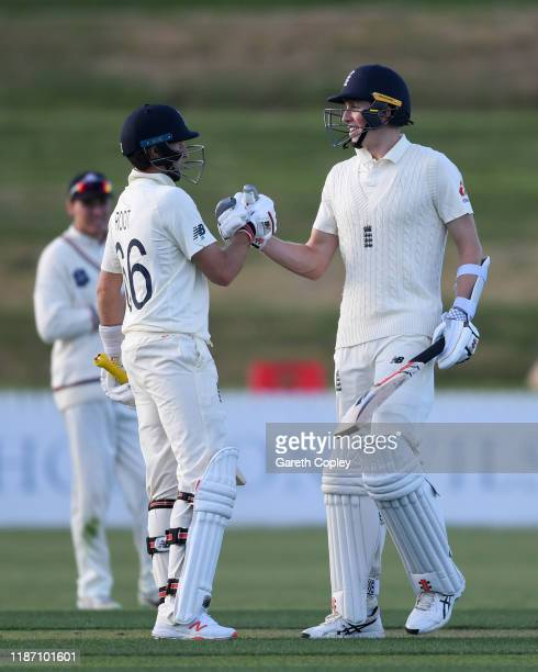 Zak Crawley of England celebrates with captain Joe Root after reaching his century during the tour match between New Zealand XI and England at Cobham...