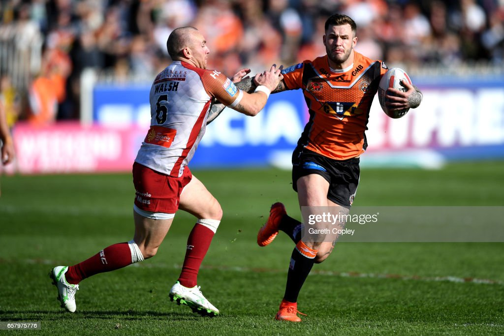 Zak Hardaker of Castleford hands off Luke Walsh of Catalans during the Betfred Super League match between Castleford Tigers and Catalans Dragons at Wheldon Road on March 26, 2017 in Castleford, England.