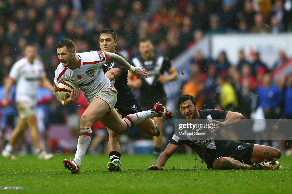 Zak Hardaker of England skips past the challenge of Peta Hiku of New Zealand during the third International Rugby League Test Series match between England and New Zealand at DW Stadium on November 14, 2015 in Wigan, England.