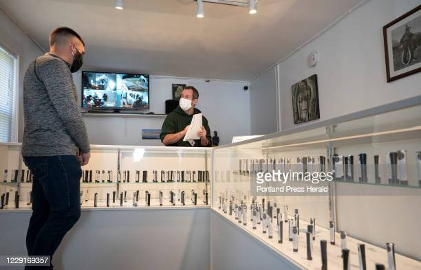 Zak Hollingshead, left, talks with John Lorenz about the pre-rolled marijuana joint options at Lorenz's recreational marijuana store in Northport on...