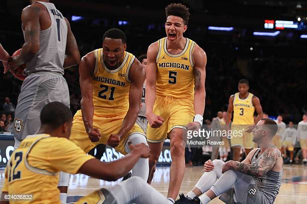 Zak Irvin and DJ Wilson of the Michigan Wolverines celebrate with MuhammadAli AbdurRahkman after a foul against the Marquette Golden Eagles in the...