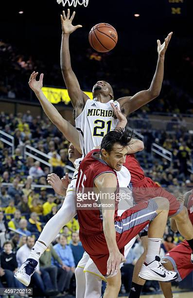 Zak Irvin of the Michigan Wolverines looses the ball after colliding with Sam McBeath of the Nicholls State Colonels during the first half at Crisler...