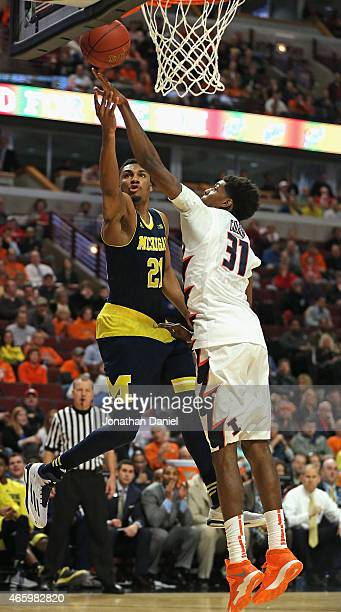 Zak Irvin of the Michigan Wolverines puts up a shot against Austin Colbert of the Illinois Fighting Illini during the second round of the 2015 Big...