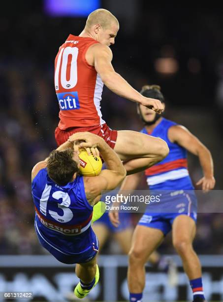 Zak Jones of the Swans bumps Travis Cloke of the Bulldogs during the round two AFL match between the Western Bulldogs and the Sydney Swans at Etihad...