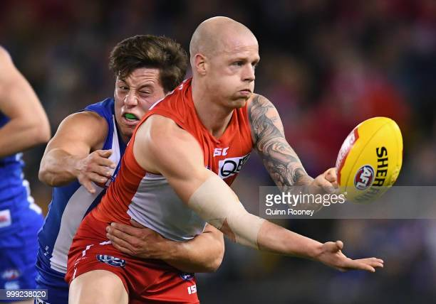 Zak Jones of the Swans handballs whilst being tackled by Nathan Hrovat of the Kangaroos during the round 17 AFL match between the North Melbourne...