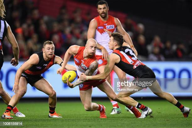 Zak Jones of the Swans handballs whilst being tackled by Orazio Fantasia of the Bombers during the round 19 AFL match between the Essendon Bombers...
