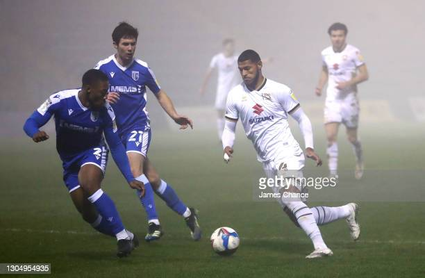 Zak Jules of Milton Keynes Dons is challenged by Ryan Jackson and Thomas O'Connor of Gillingham FC during the Sky Bet League One match between...