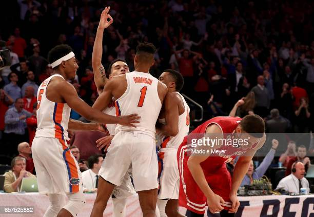 Zak Showalter of the Wisconsin Badgers reacts as Chris Chiozza of the Florida Gators celebrates with his teammates after hitting the game winning...