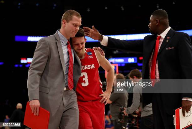 Zak Showalter of the Wisconsin Badgers reacts with his coaches after being defeated by the Florida Gators with a score of 84 to 83 in overtime during...
